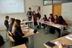 Na zdjęciu widać marszałka i uczestników debaty. Są nimi licealiści siedzący na przeciw siebie w trzyosobowych drużynach.